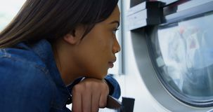 Woman looking at washing machine at laundromat 4k. Thoughtful woman looking at washing machine at laundromat 4k stock video