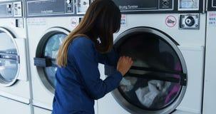 Woman looking at washing machine 4k. Woman looking at washing machine at laundromat 4k stock video footage
