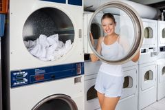 Woman Looking Through Washing Machine Lid. Portrait of young woman in undergarments looking through washing machine lid at laundromat Royalty Free Stock Photo