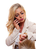 Woman looking at watch. A attractive woman is looking at her watch while talking on her cell phone stock photography
