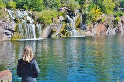 A woman looking at waterfalls. A blond woman looking at several waterfalls cascading down rocks into a lake Stock Photos