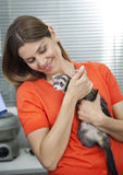 Woman Looking At Weasel In Veterinary. Happy mid adult woman looking at weasel in veterinary Stock Photography