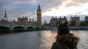 Woman looking at Westminster palace at sunset Stock Images