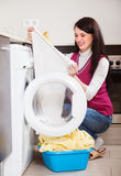 Woman looking white clothes near washing machine Royalty Free Stock Photo