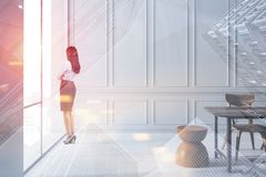 Woman looking in white dining room window stock photography