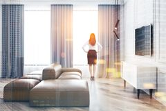 Woman looking in white living room window stock images