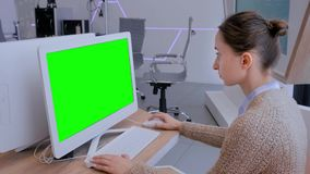 Woman looking at white monitor of desktop computer with blank green display. In modern futuristic office interior. Mock up, copyspace, workspace, chroma key stock video footage