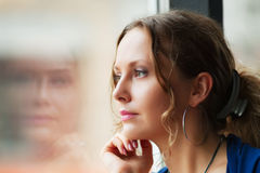 Sad woman looking out window. Beautiful sad young woman looking through the window Stock Image