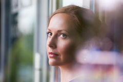 Sad woman looking through a window Royalty Free Stock Photo