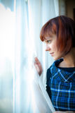 Woman Looking Through The Window Royalty Free Stock Photography