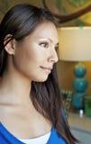 Woman looking through window. Beautiful young woman looking through window of bedroom Stock Image