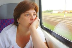 The woman is looking into window. Of train Royalty Free Stock Image