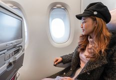 Woman looking at the window of airplane in flight time stock photo
