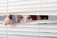 Woman looking through window blinds stock photography