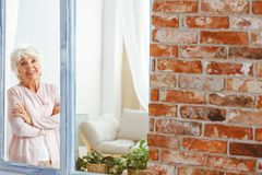 Woman looking through the window. Happy smiling confident woman looking through the window in her apartment Royalty Free Stock Image