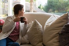 Woman looking through window while having coffee Royalty Free Stock Photography