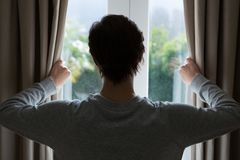 Woman looking through window at home. Rear view of woman looking through window at home Stock Photography