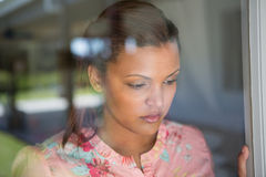 Woman looking through window at home. Thoughtful woman looking through window at home Royalty Free Stock Photos