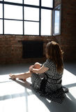 Woman looking through the window. Photo of a woman sitting on the floor and looking through the window. Portrait photography Royalty Free Stock Photos