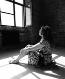 Woman looking through the window. Photo of a woman sitting on the floor and looking through the window. Portrait photography Stock Image
