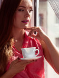 Woman looking through window, relaxing drinking coffee Stock Photos