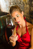 Woman looking at wine glass in the cellar Royalty Free Stock Photos
