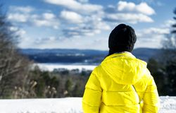 Woman looking at winter landscape in new england. A woman wearing a yellow winter jacket looking out over the landscape of the hills around the berkshires of stock image