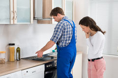 Woman Looking At Worker Repairing Induction Hob Royalty Free Stock Photos
