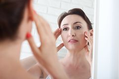 Woman looking at wrinkles in mirror. Plastic surgery and collage stock image