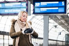 Woman looking at wristwatch in train station as her train has a delay. She is impassionate and late royalty free stock image