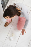 Woman Looking At Yoghurt Spilled On The Floor Royalty Free Stock Photography