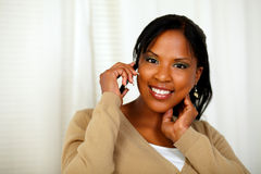 Woman looking at you while talking on cellphone Royalty Free Stock Photo