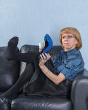 Woman looking your shoes on couch Royalty Free Stock Photography
