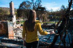 Woman lookinh at her burned home after fire disaster. Young owner woman checking burned and ruined house and yard after fire, consequences of fire disaster stock image