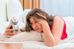 Woman looks at an alarm clock Stock Images