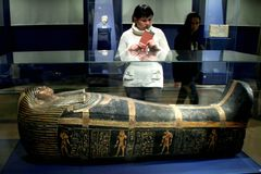 A woman looks at an ancient Egyptian sarcophagus. Royalty Free Stock Image