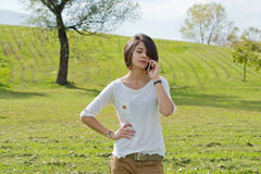 Woman looks annoyed while talking on the phone Stock Photos