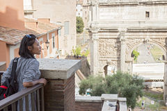 Woman looks at the Arch of Septimius Severus. Roma, Italy Royalty Free Stock Photo