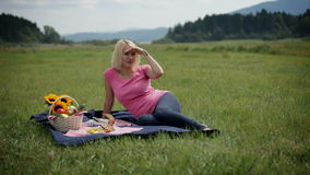Woman looks around while lying on picnic blanket with goods around. Woman resting on a blanket trying to relax and enjoy the sight and the nature around her stock video footage
