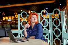 A woman looks away thoughtfully with glasses in hand behind a stellite in a cafe. A woman, aged, red-haired, in a blue dress and glasses, looks away thoughtfully Stock Photos