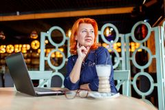 The woman looks away thoughtfully and holds a hand at the chin sitting at a table in a cafe. A woman, aged, red-haired, in a blue dress and glasses, looks away Stock Photo