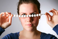 Woman looks through a beads Stock Photo
