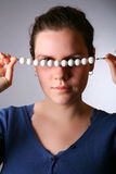 Woman looks through a beads Royalty Free Stock Image