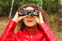 Woman looks through binoculars outside Royalty Free Stock Photos