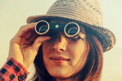 Woman looks through binoculars Royalty Free Stock Photography
