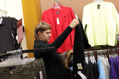 Woman looks at black jacket Stock Photography