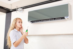 Woman looks at a broken air conditioner Stock Photo