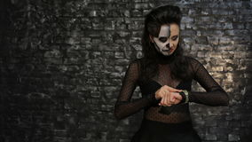 Woman looks at the clock and angry. A woman looks at the clock and angry. Beautiful woman with make-up skeleton posing on black background of a brick wall stock video