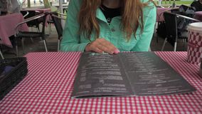 A woman looks closely at the menu in the cafe, chooses a dish for dinner. stock video footage