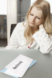 Woman looks dejected on invoice Stock Photography